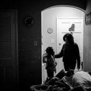 mother stands with child in doorway